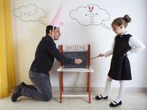 Liten flickaundervisningmatematik till en vuxen dumhuvud royaltyfri foto