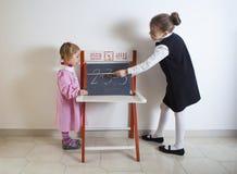 Liten flickaundervisningmatematik till ett mer ung barn arkivfoto