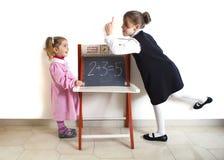 Liten flickaundervisningmatematik till ett mer ung barn royaltyfri bild