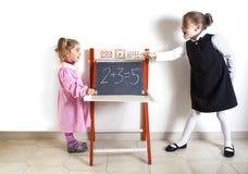 Liten flickaundervisningmatematik till ett mer ung barn royaltyfria bilder