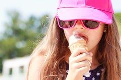 Liten flickaunge som äter glass på stranden Sommar Arkivfoto