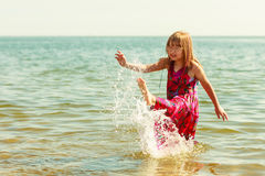 Liten flickaunge som plaskar i havshavvatten Gyckel Arkivbild