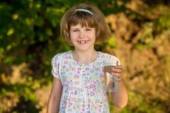 Liten flickaungen med exponeringsglas av vatten i morgon, dricker varje dag fotografering för bildbyråer
