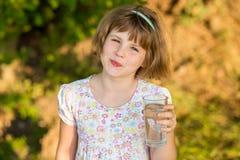 Liten flickaungen med exponeringsglas av vatten i morgon, dricker varje dag arkivbilder