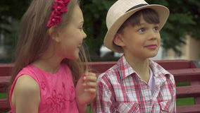 Liten flickaviskning i pojke` s gå i ax på bänken lager videofilmer