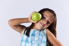 Liten flickavisning ett grönt äpple royaltyfria bilder