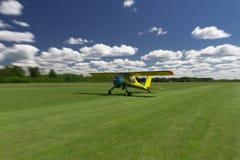Liten flygplanlandning eller ta av på en gräsluftremsa med rörelsesuddighet för att framföra rörelse Royaltyfri Foto