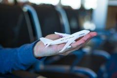 Liten flygplanmodell på den manliga handen inom ett stort Arkivfoton
