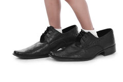 Liten fot i stora svarta skor Arkivfoton