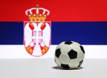Liten fotboll på det vita golvet med blå och röd färg för vit, fokuserar ut örn- och kronabilden av den serbiska nationflaggan royaltyfri foto