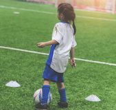 Liten fotbollflicka som utbildar sportfältet för inomhus fotboll Royaltyfri Fotografi