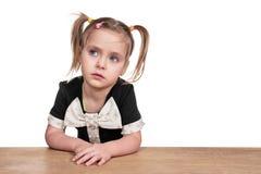 Liten frustrerad flicka på tabellen arkivbild