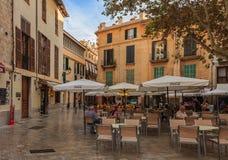 Liten fyrkant med en café för öppen luft och gamla byggnader i bakgrunden i den gamla staden i Palma de Mallorca, Spanien arkivfoto