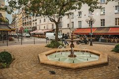 """Liten fyrkant med springbrunnen, träd och restauranger i mitt av den mer """"Quartier Latin†en i Paris arkivbild"""