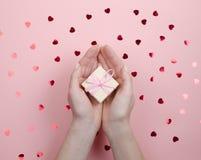 Liten gåva i hand på rosa bakgrund arkivfoton