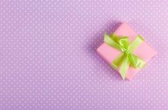 Liten gåva med en pilbåge på en försiktig purpurfärgad bakgrund Arkivfoton