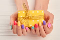 Liten gåvaask i kvinnlig manicured händer arkivbilder