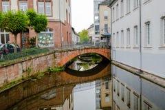 Liten gammal bågebro med härlig reflexion i Saarburg, Tyskland arkivbild