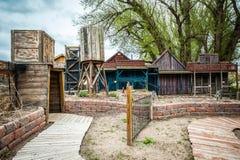 Liten gammal stad med träbyggnader och ingång till en min Royaltyfri Bild