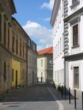 Liten gata med stenläggning och gamla byggnader Royaltyfria Bilder