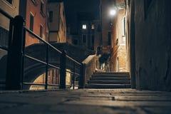Liten gata och bro på natten i Venedig, Italien Arkivbilder