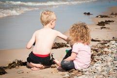 Liten giirl håller ögonen på hennes broder undersökning och att spela i havet Royaltyfri Bild