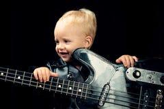 Liten gitarrist i vippaomslag Little rockstjärna Barnpojke med gitarren Vagga stilbarnet vagga och royaltyfri foto