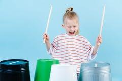 Liten glad pojke som använder trumpinnar på järn och plast- hinkar Spela rytm royaltyfria bilder