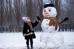 Liten gladlynt flicka nära den stora roliga snögubben Den gulliga lilla flickan har gyckel i vinter parkerar arkivbild