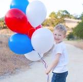 Liten gladlynt pojke som rymmer färgrika ballonger och firar 4t Royaltyfri Bild