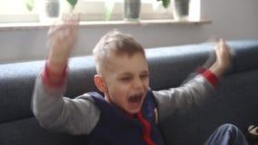 Liten gladlynt pojke som vinkar hans händer lager videofilmer