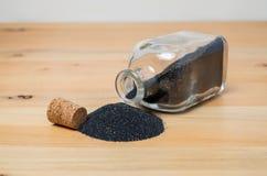 Liten glasflaska med svart sand- eller vapenpulver royaltyfri fotografi