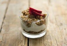 Liten glass bunke av hemlagad granola med grekisk yoghurt och jordgubbar, på den trälantliga tabellen arkivbild