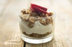 Liten glass bunke av hemlagad granola med grekisk yoghurt och jordgubbar, på den trälantliga tabellen fotografering för bildbyråer