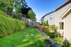 Liten gräsplan fäktad bakgård med den trevliga trädgården Arkivbild