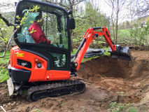 Liten grävskopa med mannen inom, på dammet för arbetsdanandeträdgård Fotografering för Bildbyråer