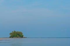 Liten grön ö i blå himmel arkivbilder