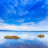 Liten grön ö två i en blåttlake under den klara skyen. Argentario Tuscany, Italien. Royaltyfri Fotografi
