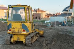 Liten gul bulldbacksikt för bakre sikt av den lilla gula bulldozern på bakgrunden av nya privata hus Fotografering för Bildbyråer