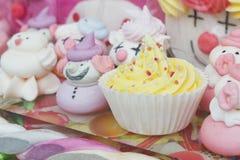 Liten gul muffin bland godisar Royaltyfri Bild