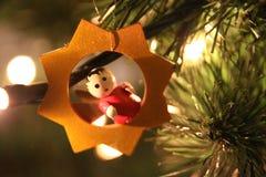 Liten gul stjärna och röd ängel på julträdet Royaltyfria Bilder