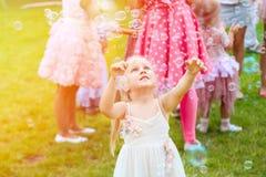 Liten gullig blond flicka i en klänning som spelar med såpbubbladuri fotografering för bildbyråer