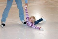 Liten gullig flicka för faderhandhjälp på isbanan arkivfoto