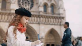 Liten gullig flicka i basker och rött halsduksammanträde nära Notre Dame och teckning skissa i Paris, Frankrike lager videofilmer