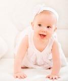 Liten gullig flicka i en vit klänning och med att le för blomma Fotografering för Bildbyråer