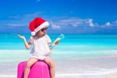 Liten gullig flicka i jultomtenhatt på resväskan på Arkivbilder