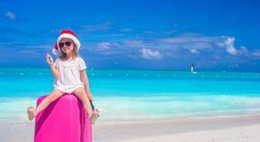 Liten gullig flicka i jultomtenhatt på resväskan på Arkivfoto