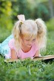 Liten gullig flicka med blont hår som läser en bok i det fria Royaltyfri Fotografi