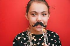 Liten gullig flicka med en girland runt om hennes hals som rymmer stöttor för en mustasch på en röd bakgrund arkivfoton
