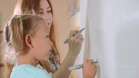 Liten gullig flicka med lärarehandstil på svart tavla i klassrum lager videofilmer